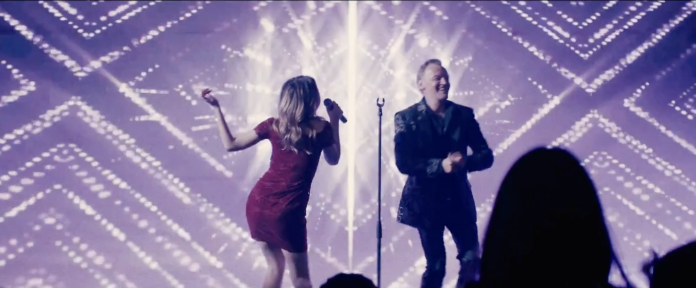A woman in a red dress and a man perform on a stage before a sleazy backdrop.