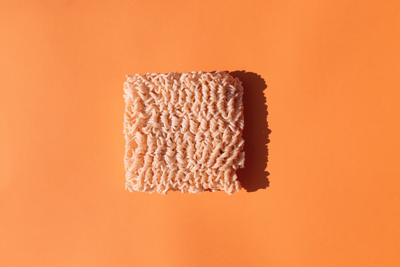 Two-minute noodles against an orange background.