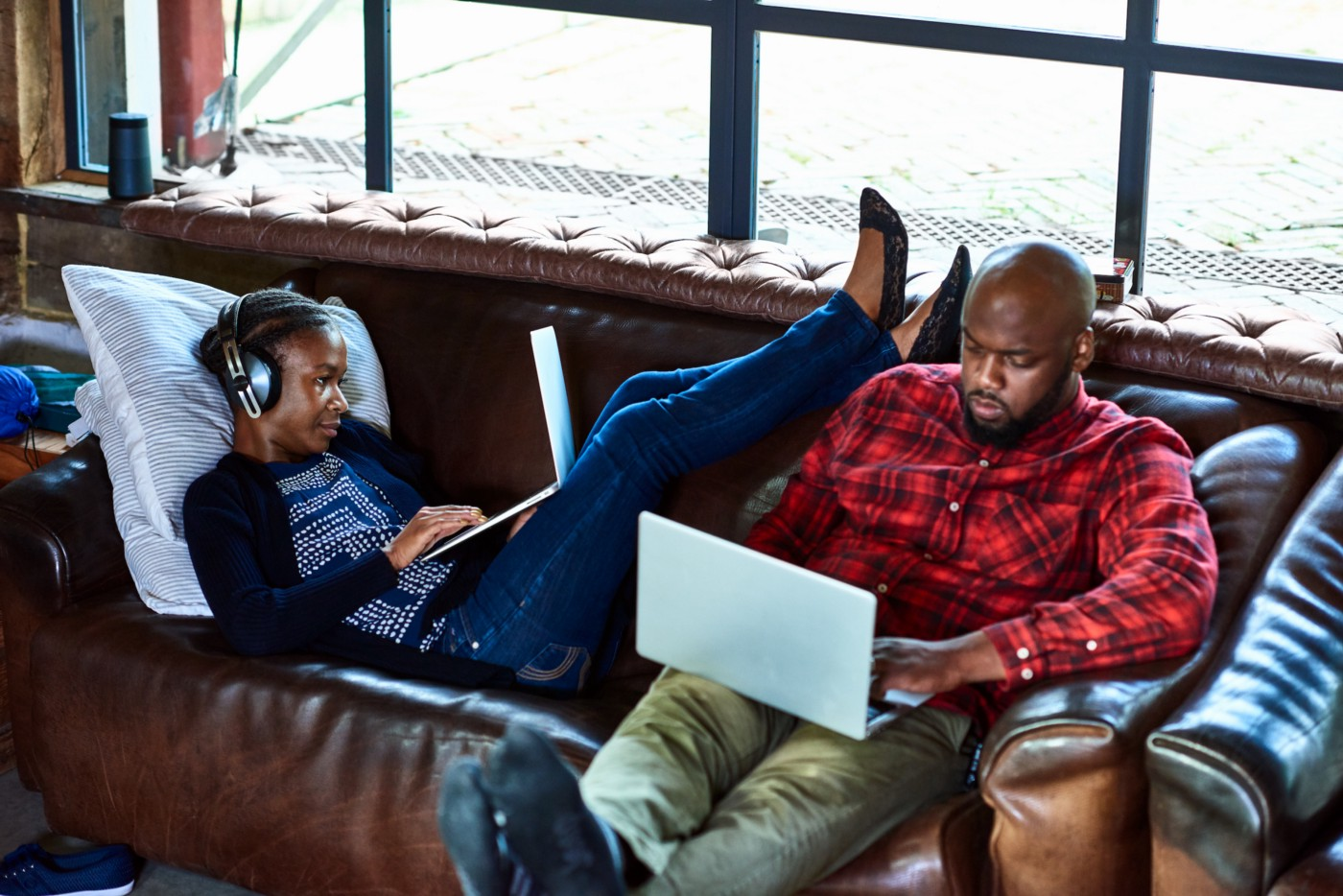 2 people sitting on a sofa working on laptops. One's reclined, resting their feet on the shoulder of the other, who's upright