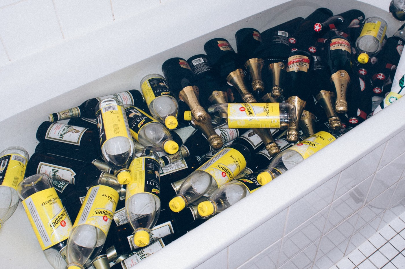 A bathtub filled with empty tonic water and gin bottles.