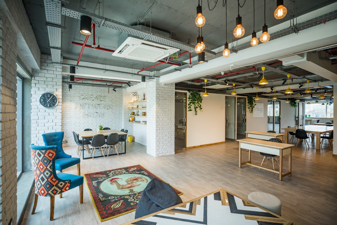 Industrial coworking office with desks, lounge chairs, and hanging ceiling lights.