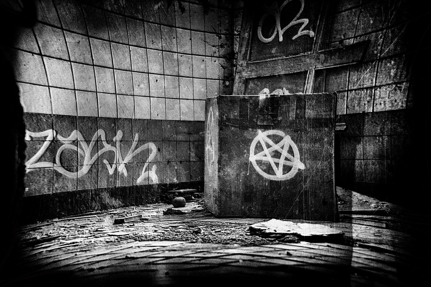 A black and white photo of an abandoned building with a pentagram spray-painted on a wall.