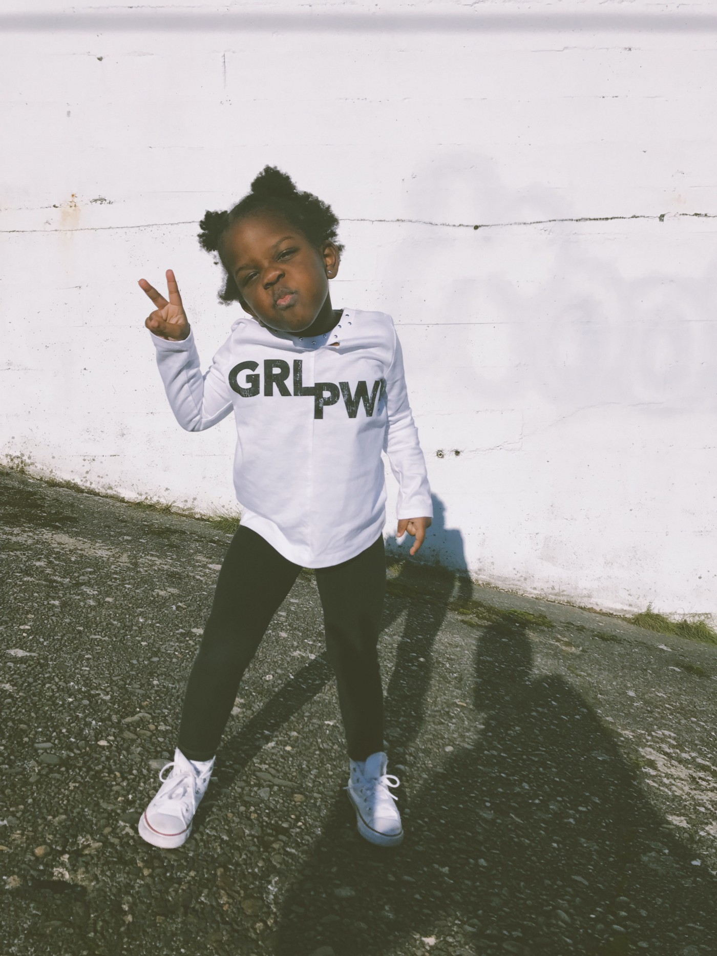 "Kiana Bosman @capturedby_kiana portrait of young Black girl holding up a ""peace sign"" & wearing tee with words ""GRL PWR."""