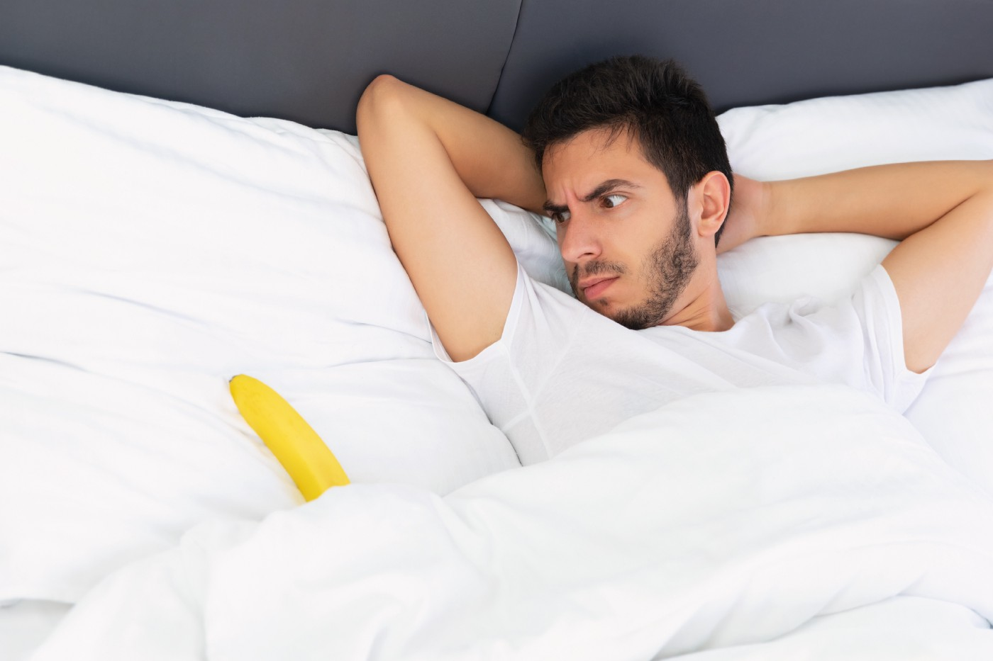 A young man in a white teeshirt looks perplexed at he stares at a banana emerging from behind the sheets