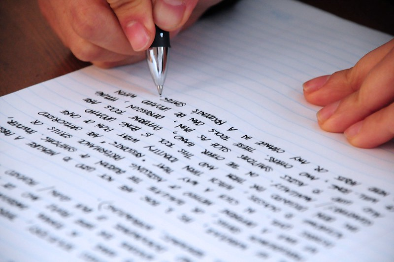 A person hand writing on a lined page