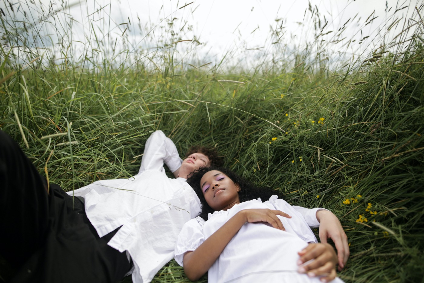 Two individuals laying in a bed of grass together with their eyes closed wearing white T-shirts