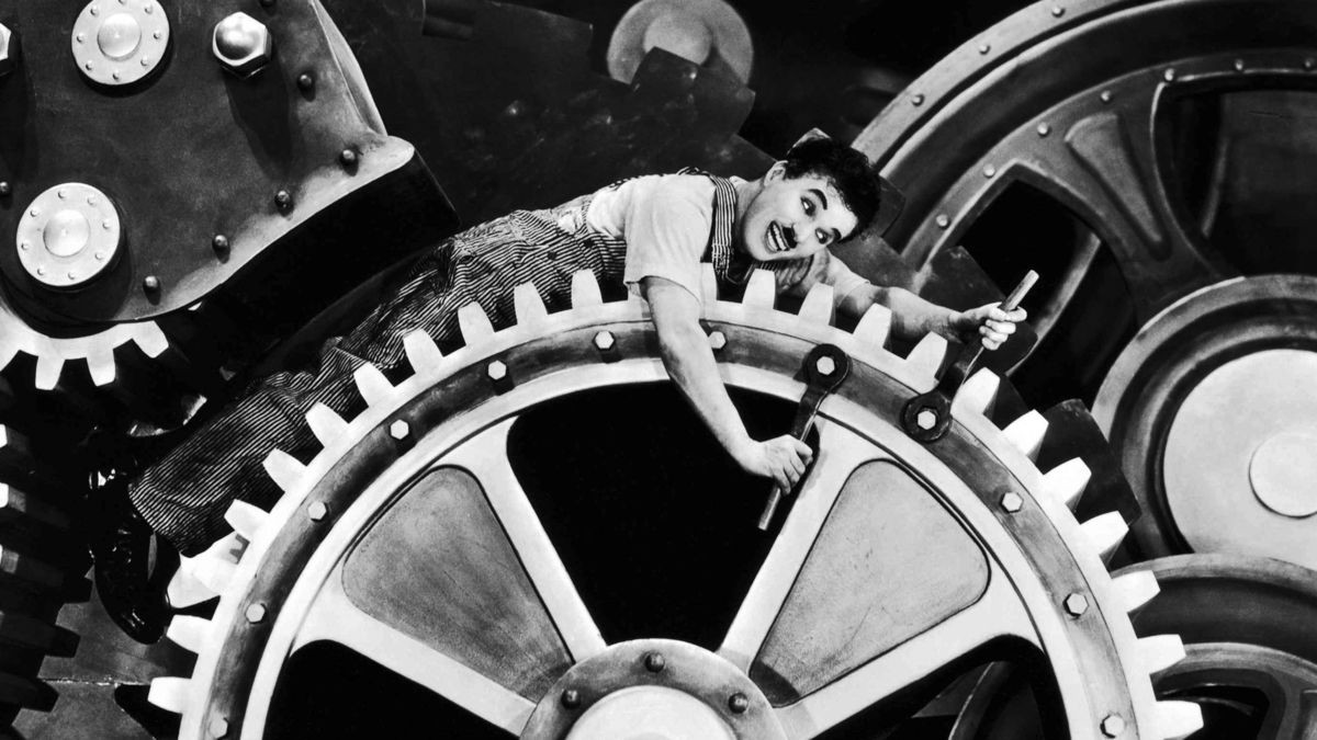 Photo from the movie Modern Times of Charlie Chaplin adjusting a large mechanical cog.
