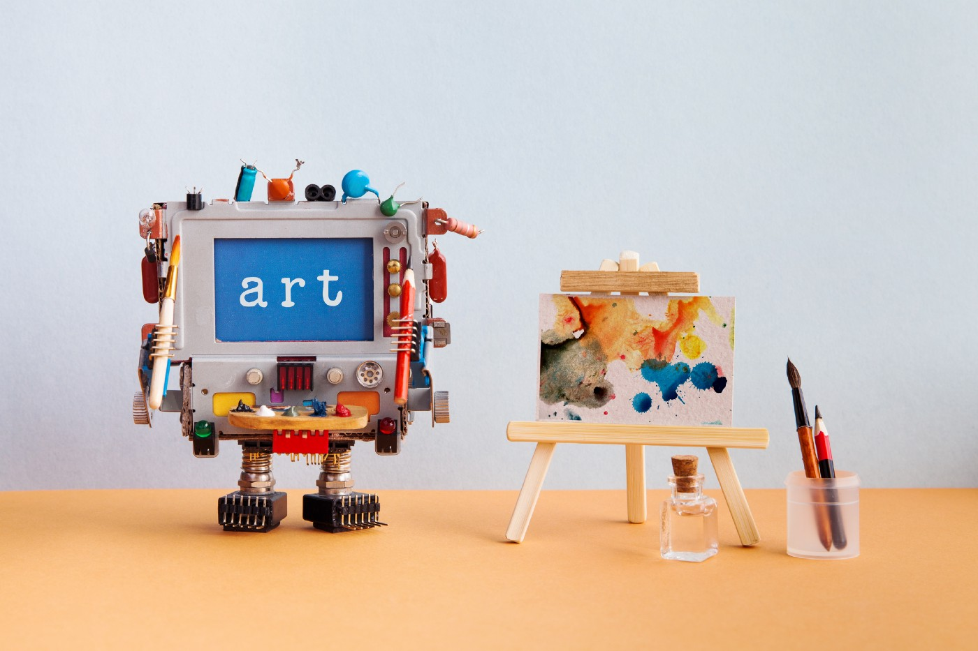 """Art"" written on a small creation made to look like a machine next to a small painting."