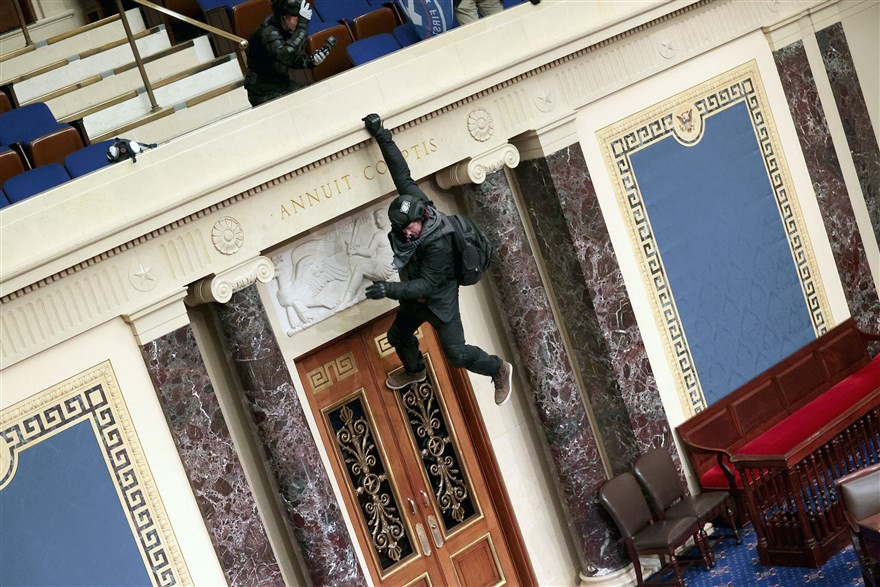 Rioter hangs from wall inside Capitol chambers.