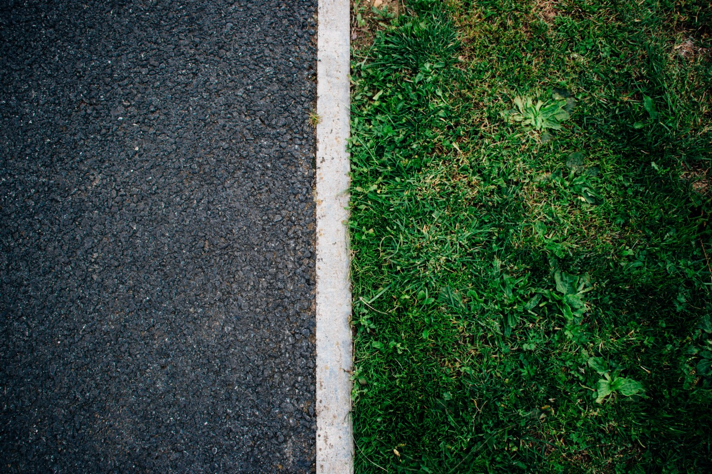 Photo of asphalt separated from grass with a white dividing line, by Will Francis on Unsplash.