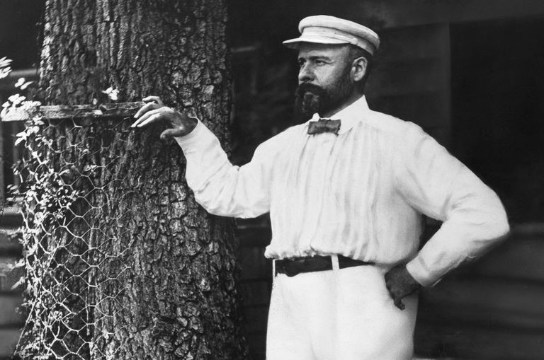 Louis Sullivan in all white standing next to a tree