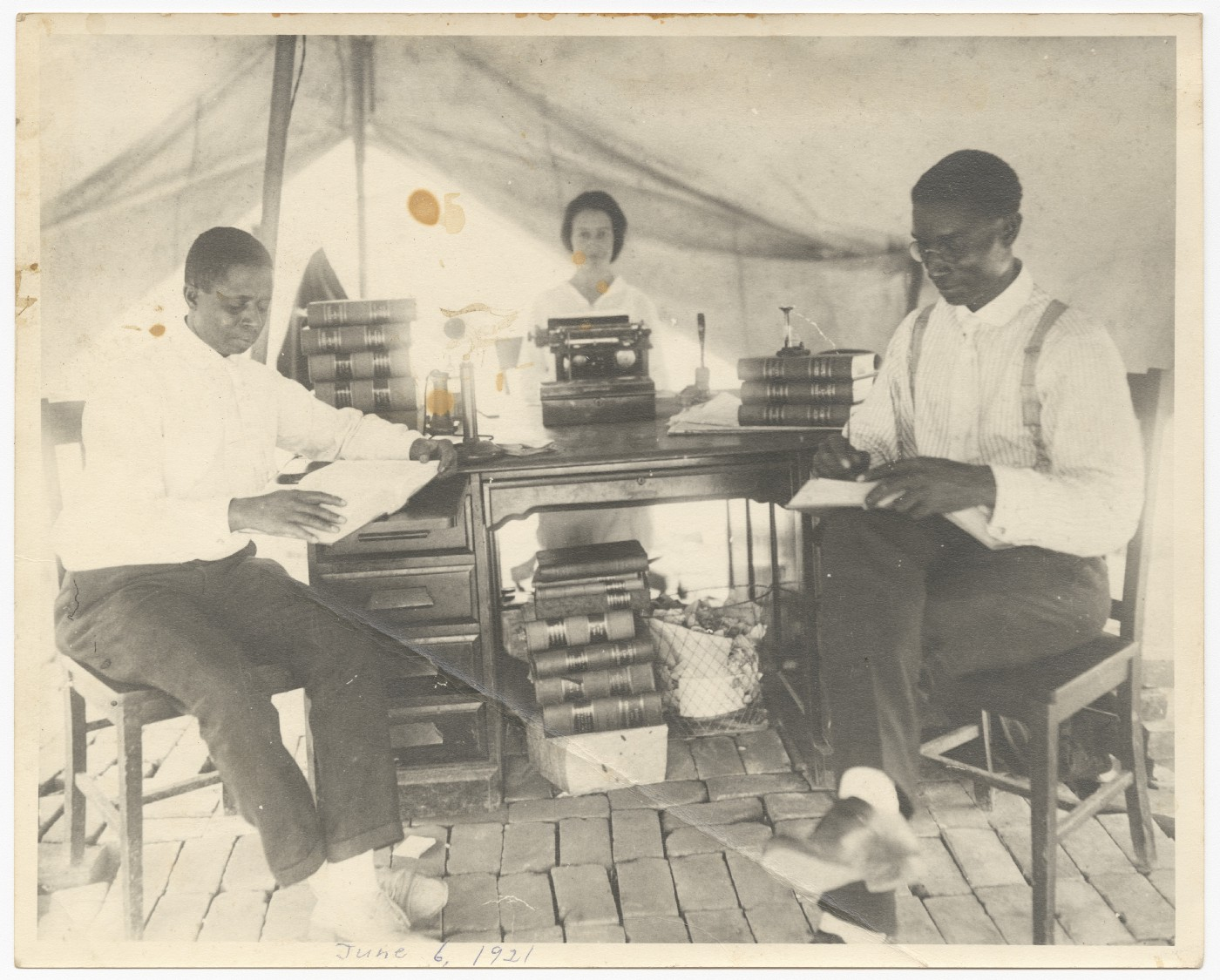 Attorney B.C. Franklin (right) sits with his partner and secretary in a makeshift law office under a tent. Tulsa 1921.