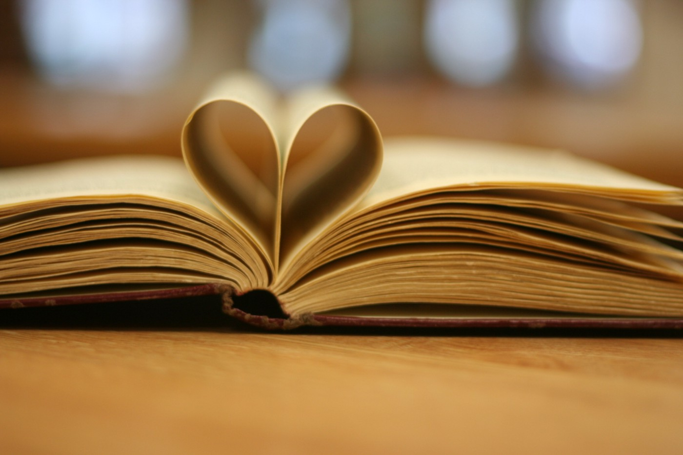 A book lies open with the middle pages gently folded into a heart shape.