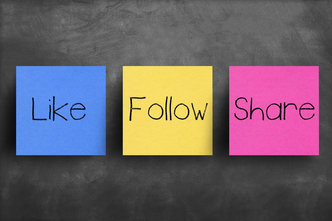 blue like, yellow follow and purple share post-it notes on black chalkboard