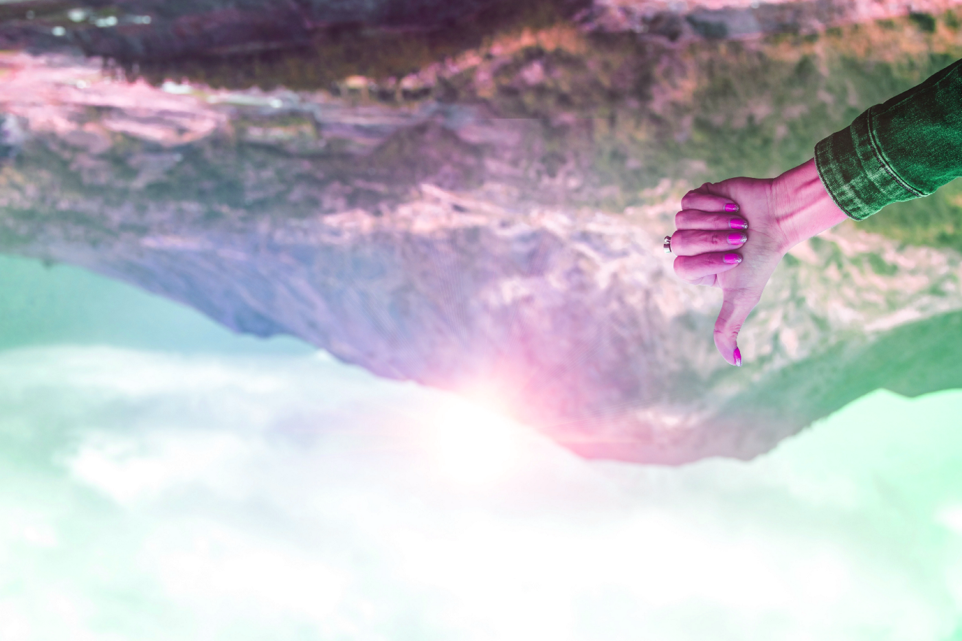 An upside-down image of a person holding their thumb up with mountains in the background.