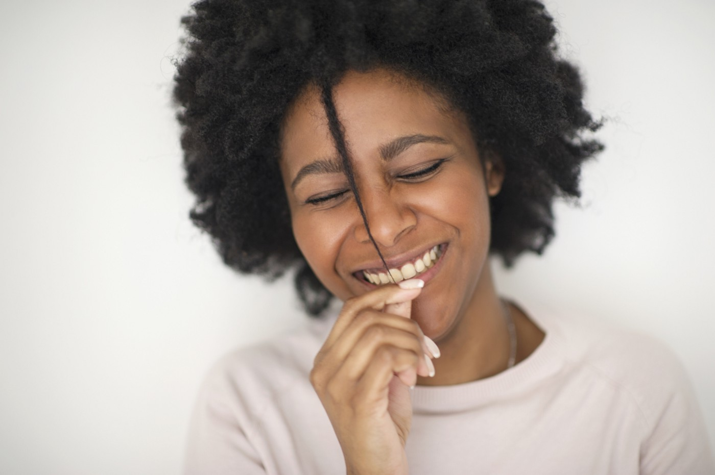 Smiling Black woman with natural hair.