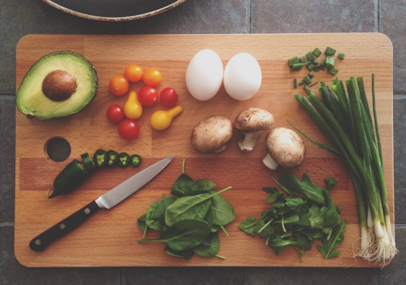 chopping board with vegetables, eggs, herbs and knife