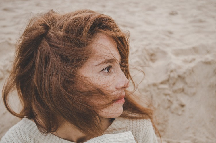 A girl with freckles on her face looking away