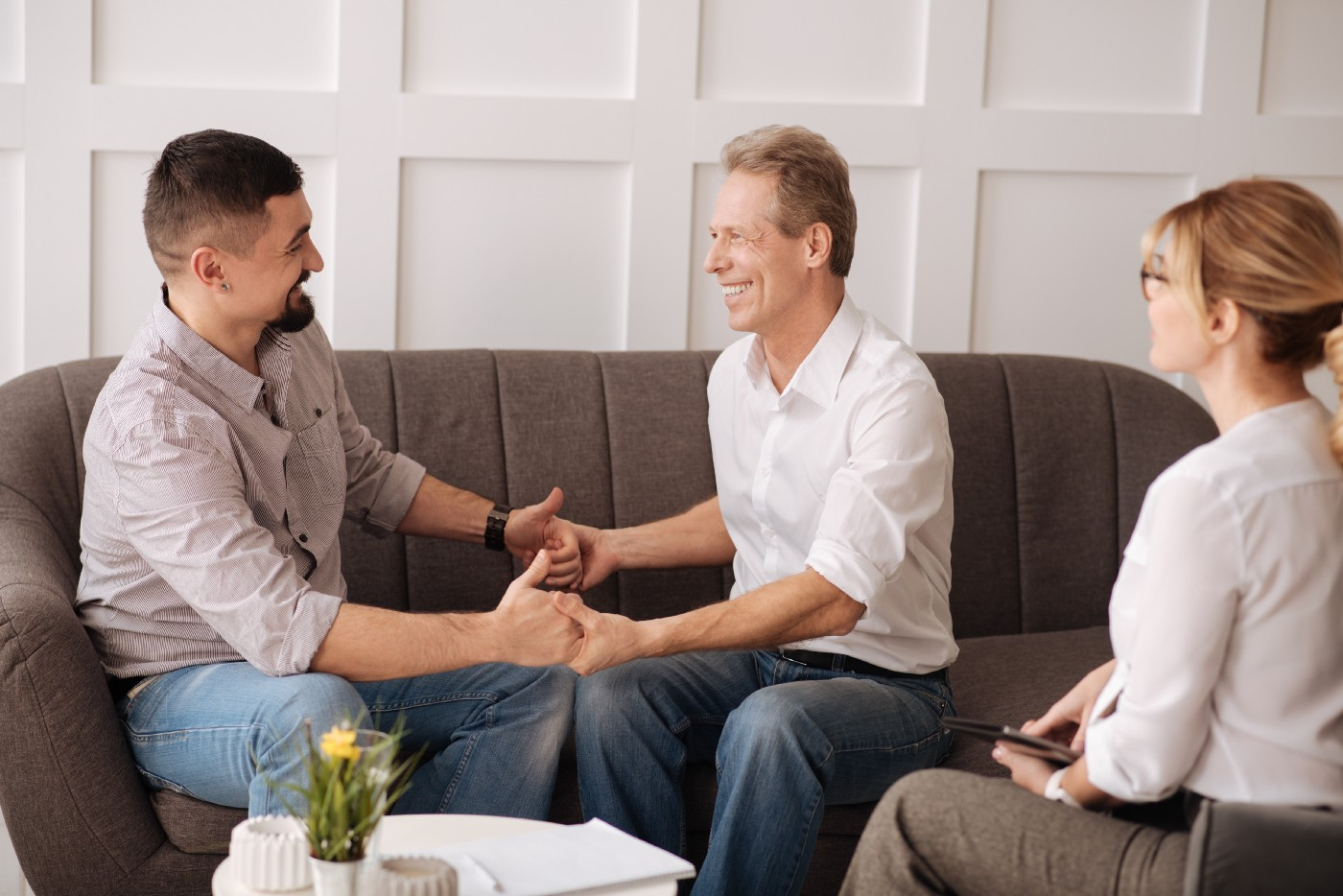 A gay couple holds hands in a therapy session and looks at each other with joy.