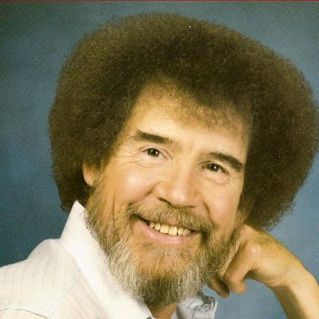 Smiling Bob Ross with beard and afro. Blue background.