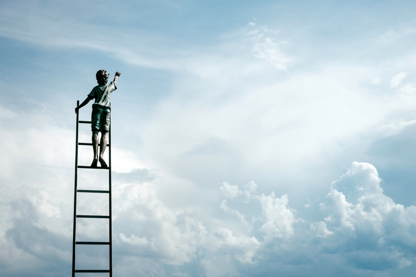 Boy on a ladder, reaching into the clouds
