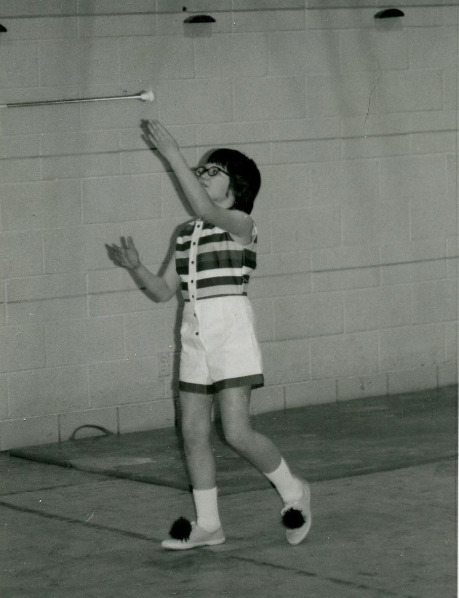 Black and white image from the mid 70's of a girl in shorts and sleeveless top tossing a baton in the air