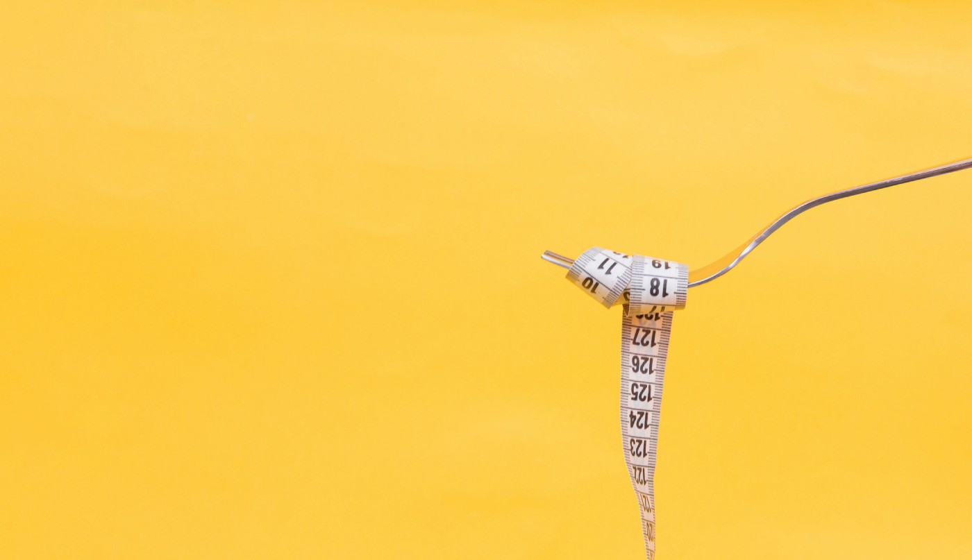 A fork wrapped up in a measuring tape to symbolise dieting