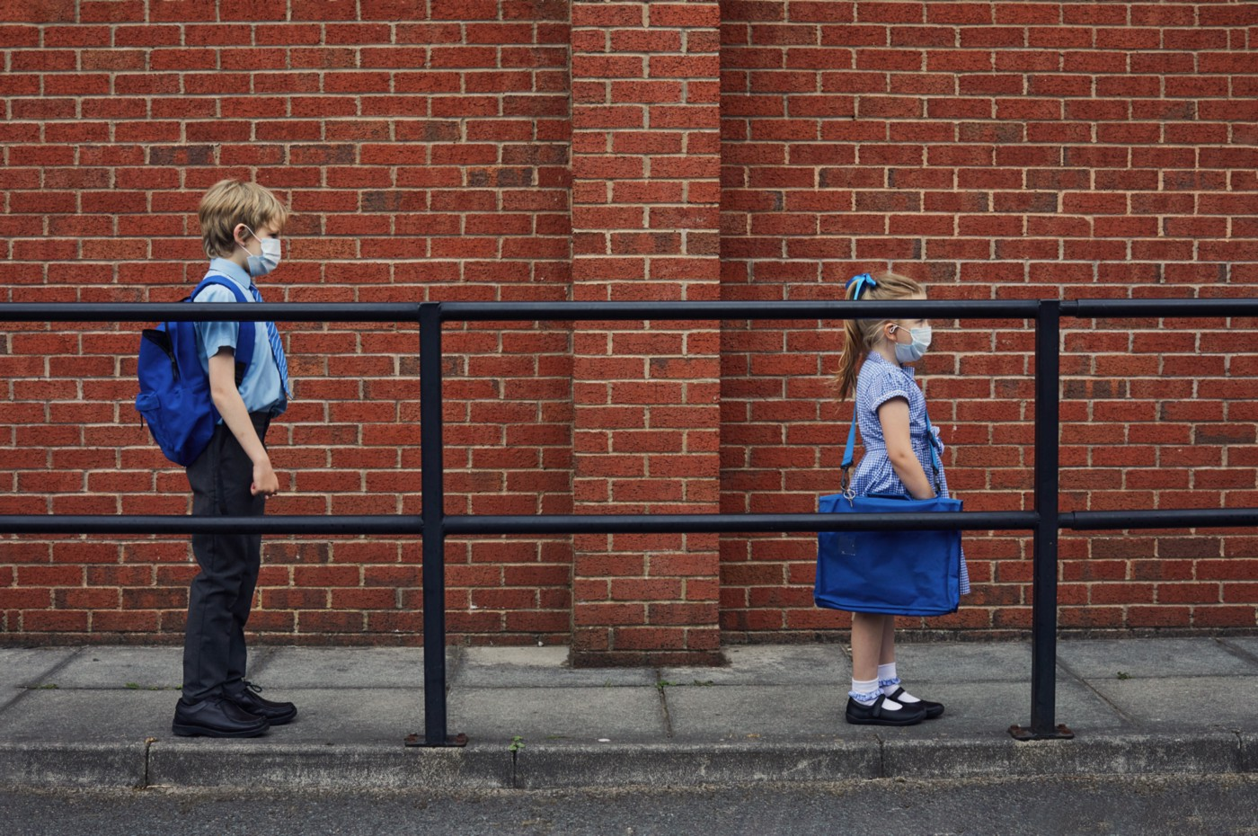 Two children wearing face masks standing six feet apart waiting in line for school.