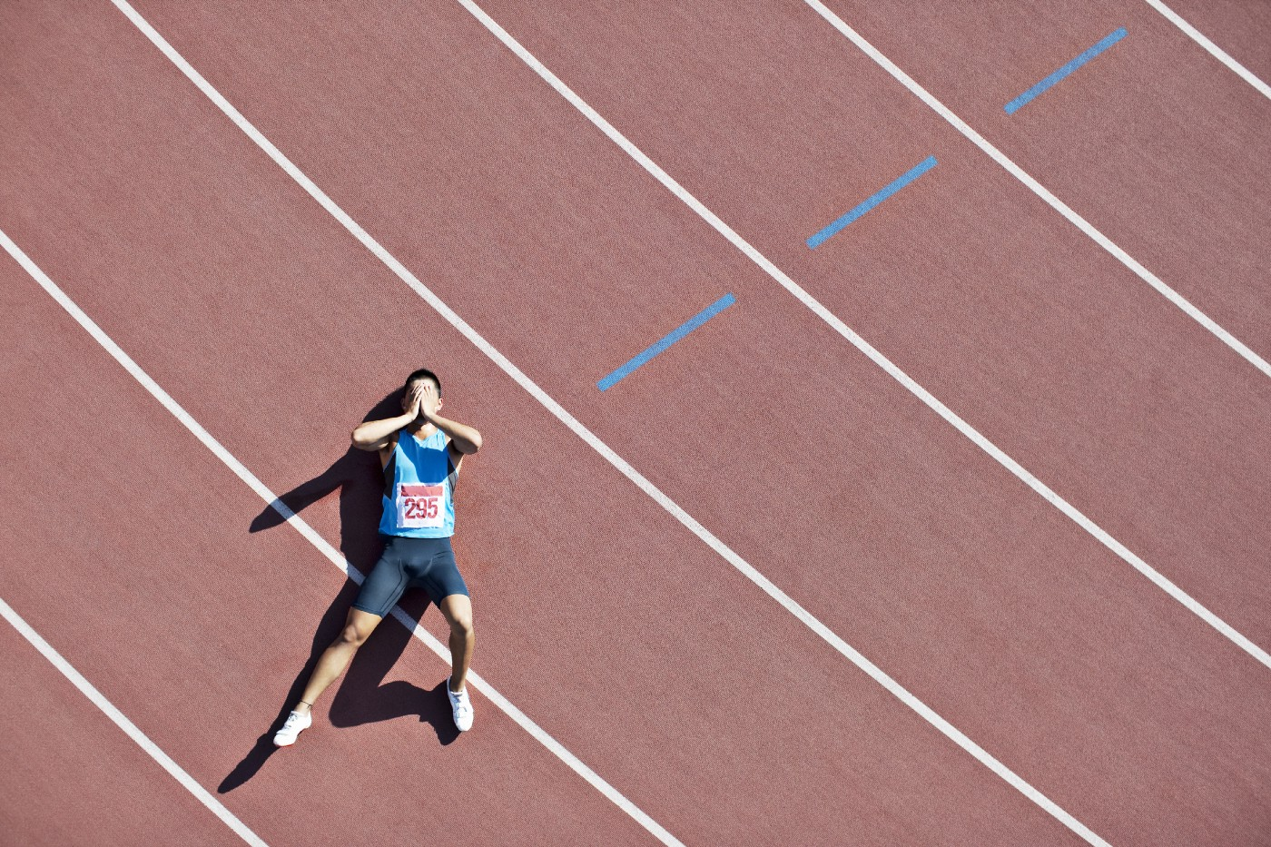 A tired runner lies down on a track.