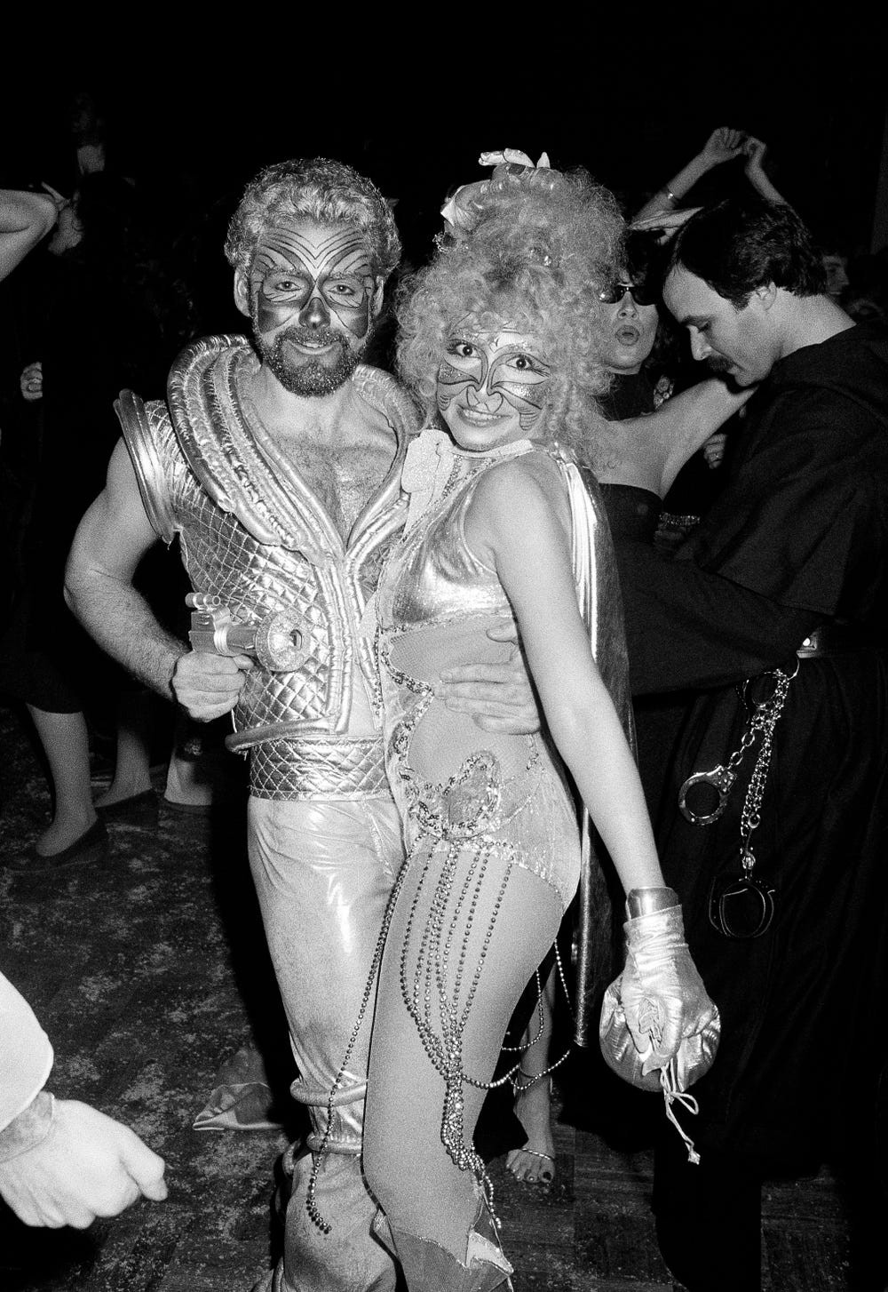 A man (left) and a woman (right) from Studio 54 close together—wearing shimmery clothes and face paint.