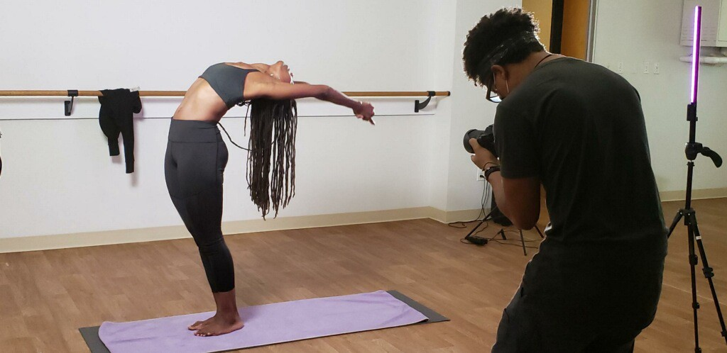 The author bends back in a yoga posture. She is being filmed for her training to become a yoga instructor.