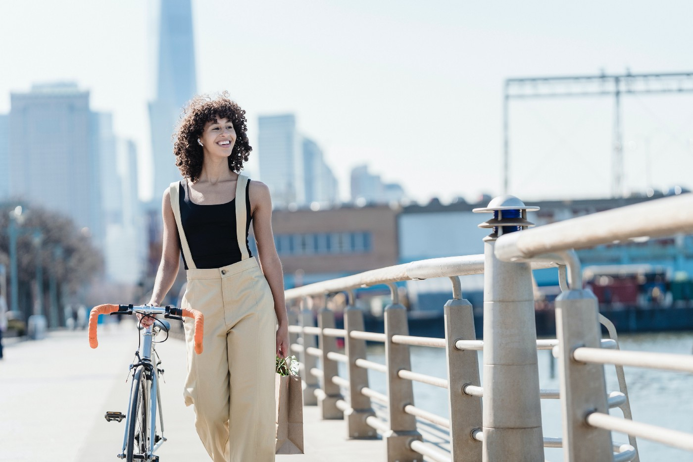 Woman walking over bridge with her right hand resting on seat of a bike that she's pushing alongside her. She has a big smile on her face with city skyline in background.