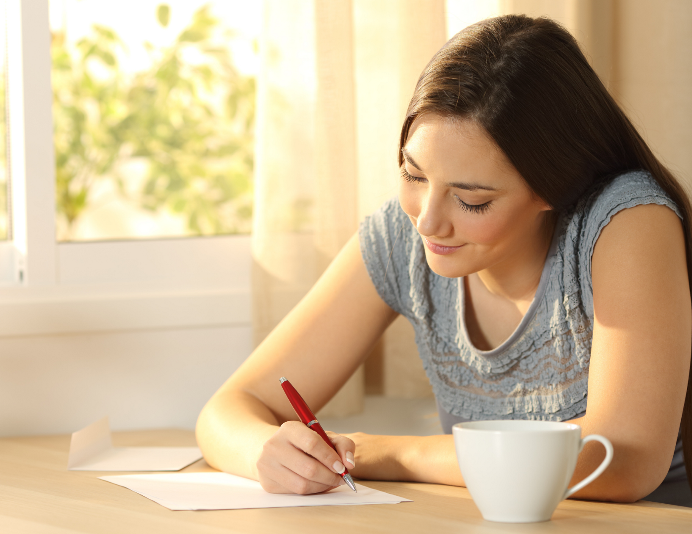 A woman seated at a table writes herself a letter.