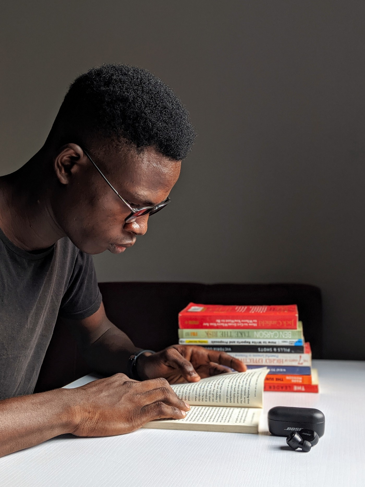 A Black man reading a book at a desk with another stack of books beside him.