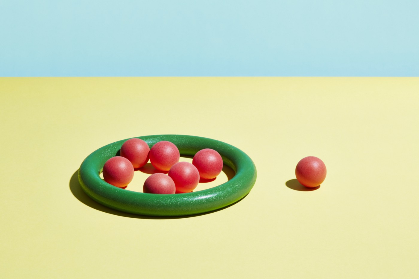 A single red sphere sits outside a group of red spheres contained within a green hoop.