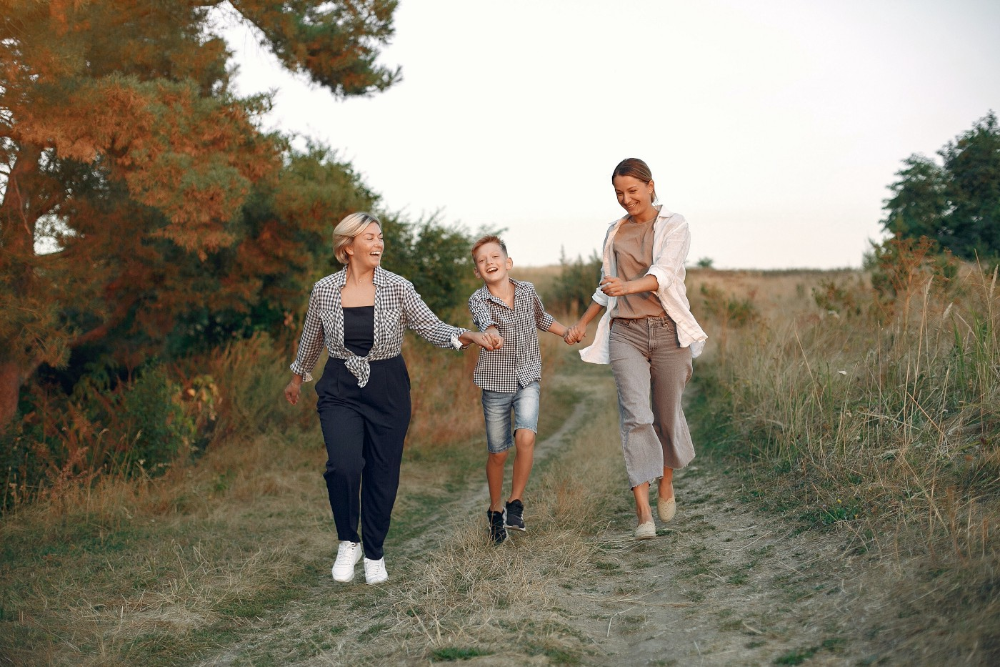 an-older-woman-with-a-younger-woman-and-a-child-running-down-a-path