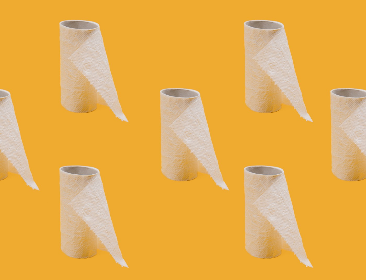 Rolls of almost used up toilet paper spaced in front of a orange background