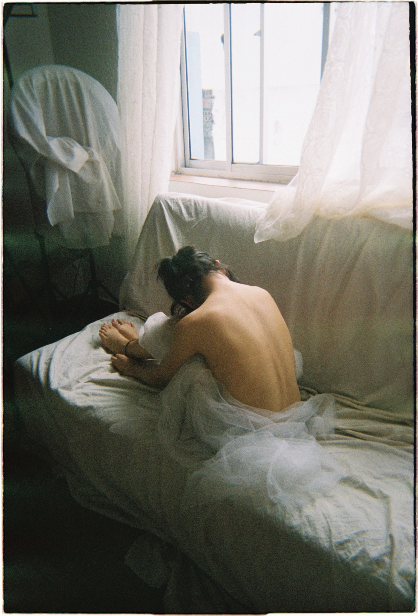 a shirtless woman with her back to us rests her head on her knees and sits on a couch bathed in soft window light