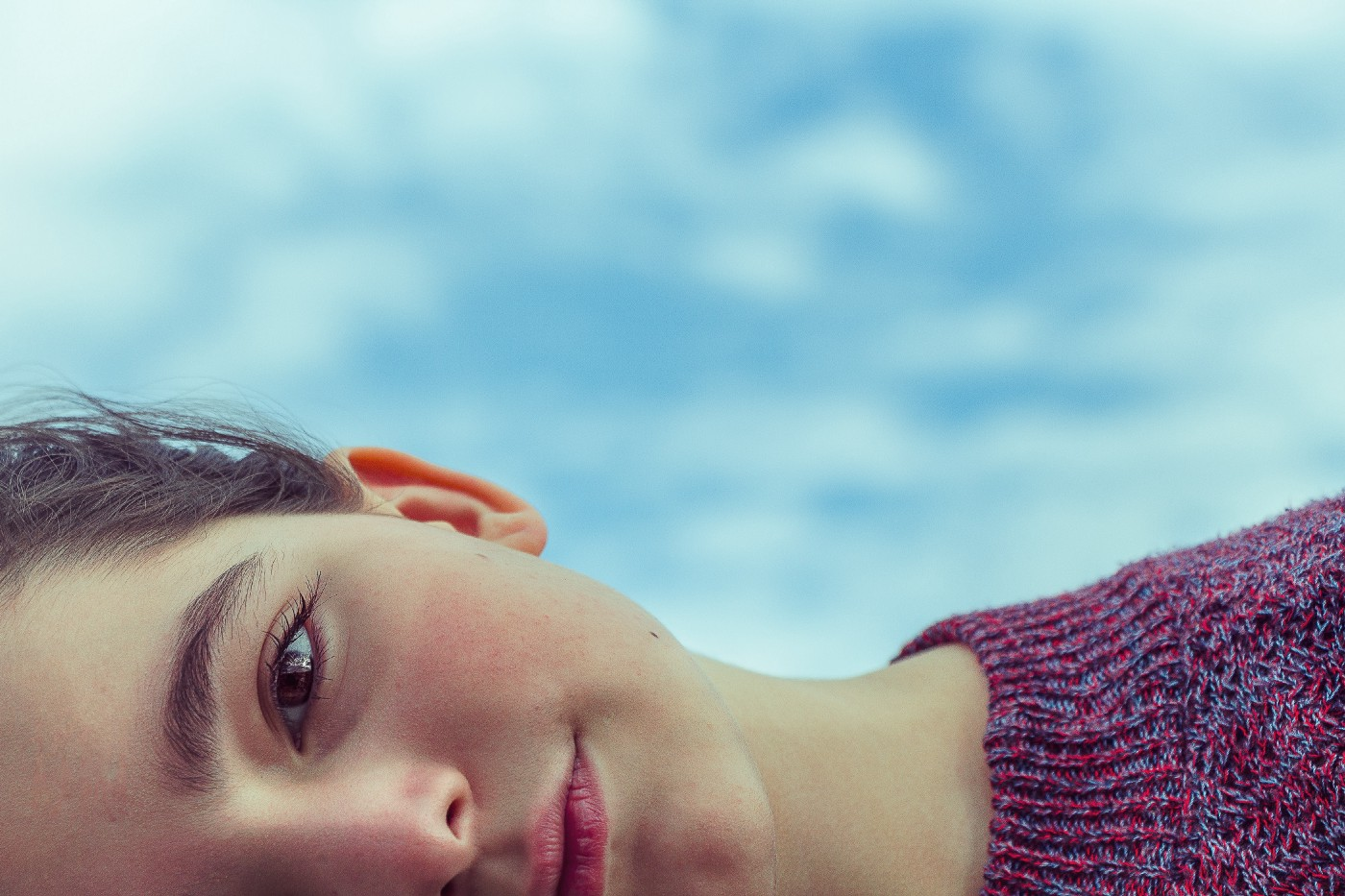 A young woman looks thoughtfully into the camera with a beautiful blue sky filled with fluffy white clouds behind her.