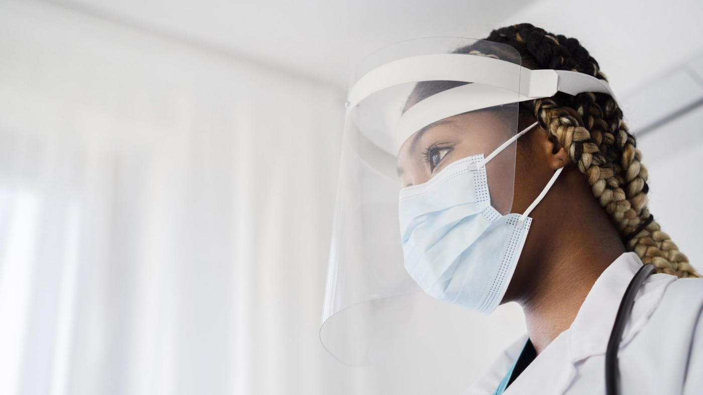 Image of a healthcare professional wearing a visor and mask.