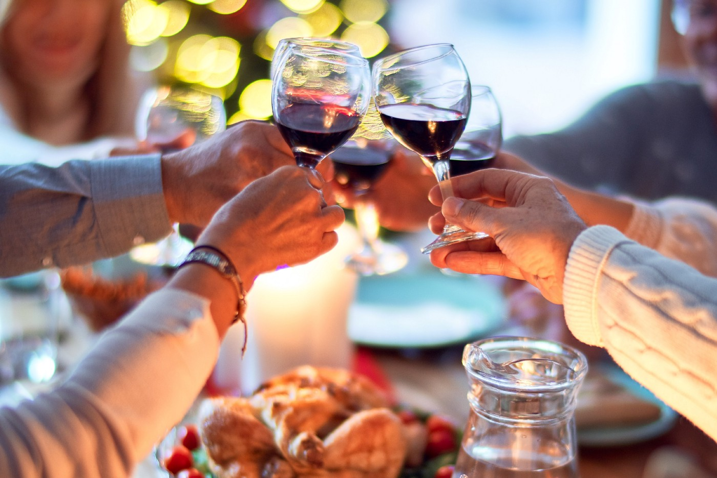 Friends raising their wine glasses in a toast around the dinner table.