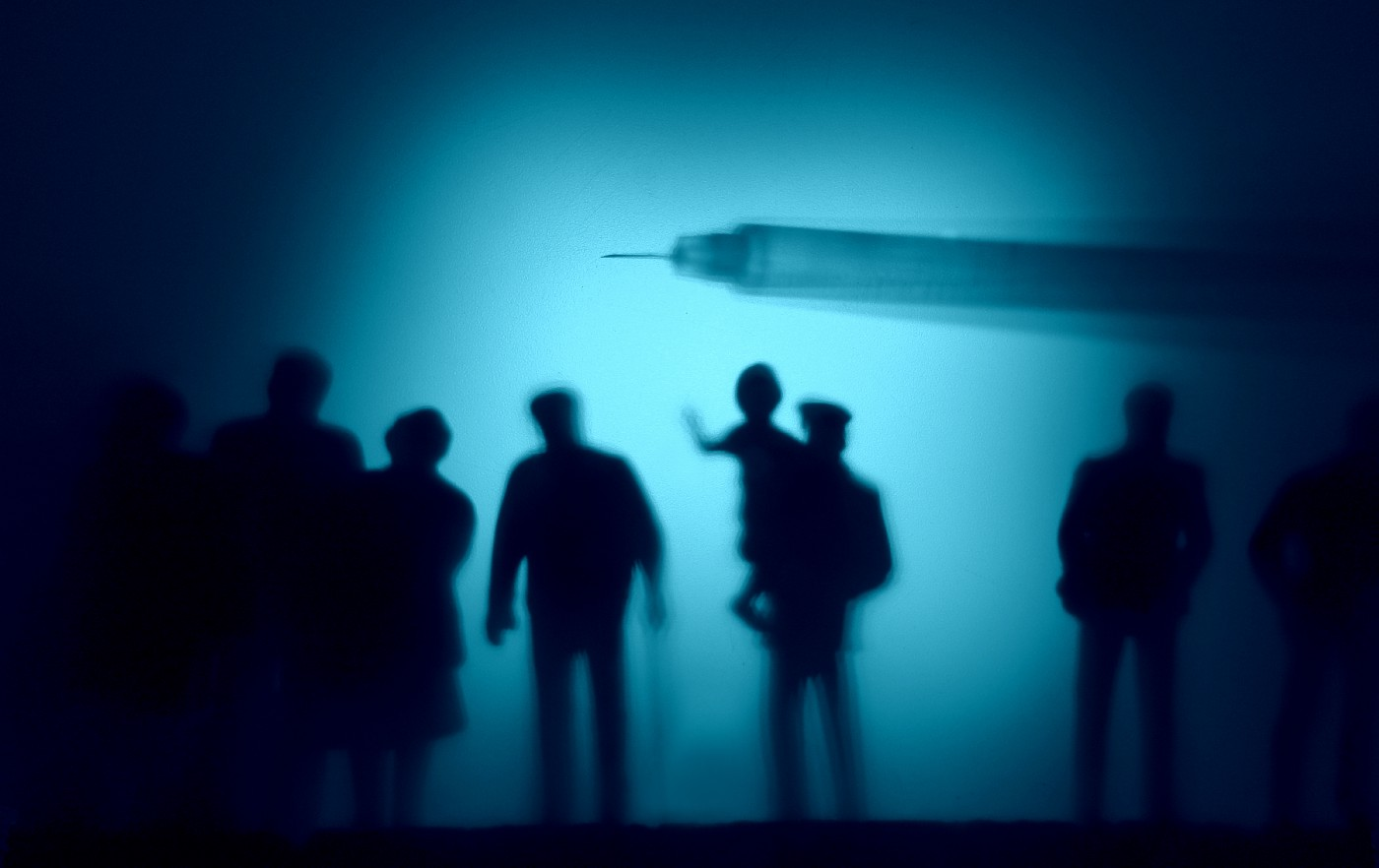 The silhouette of a vaccine shot hovering over dark silhouettes of people from various age groups.