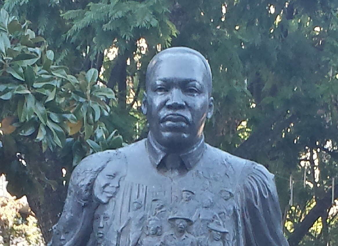 Dark colored head and shoulder statute of Martin Luther King, Jr. with trees in the background.