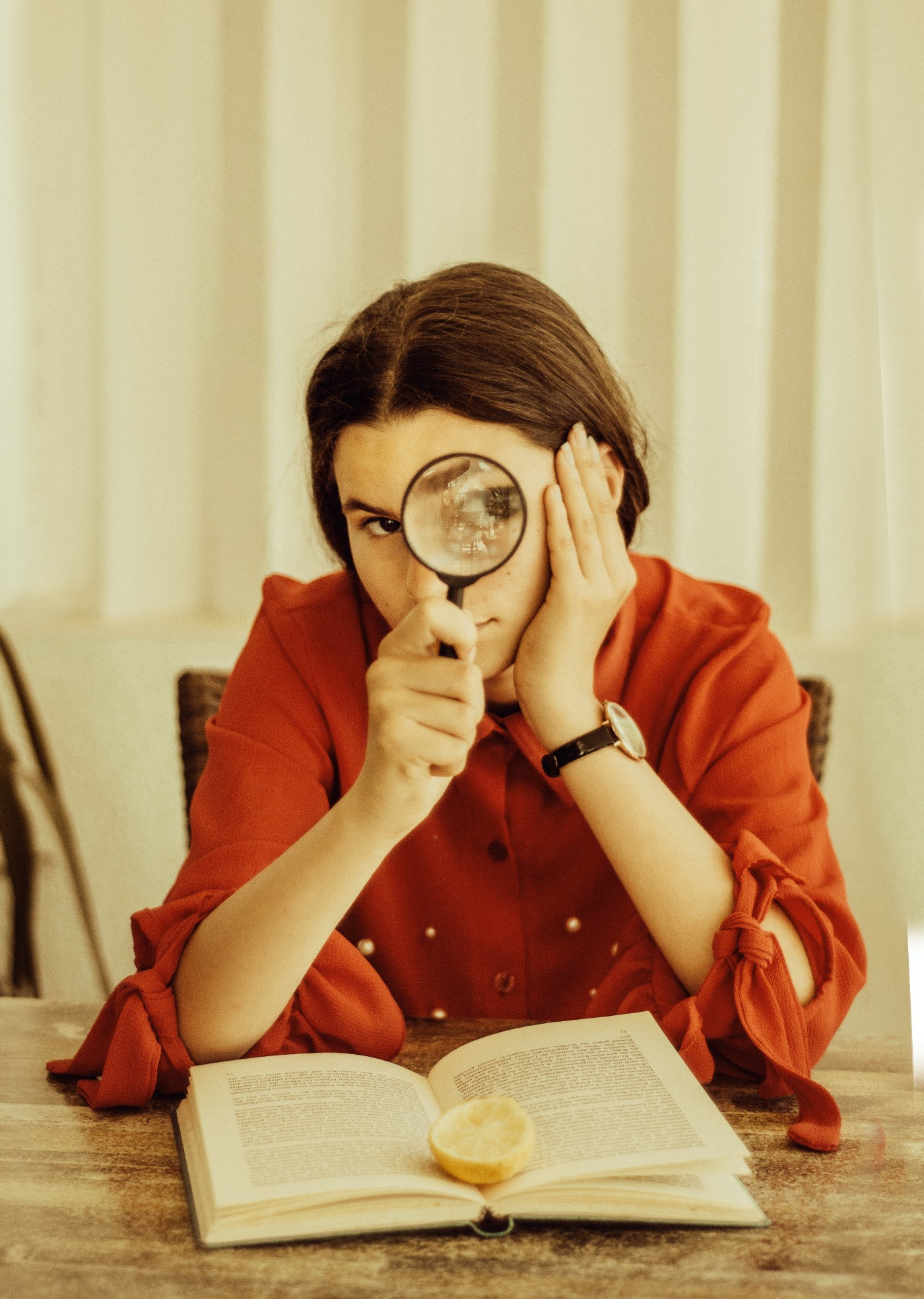Woman looking into a magnifying glass while reading a book