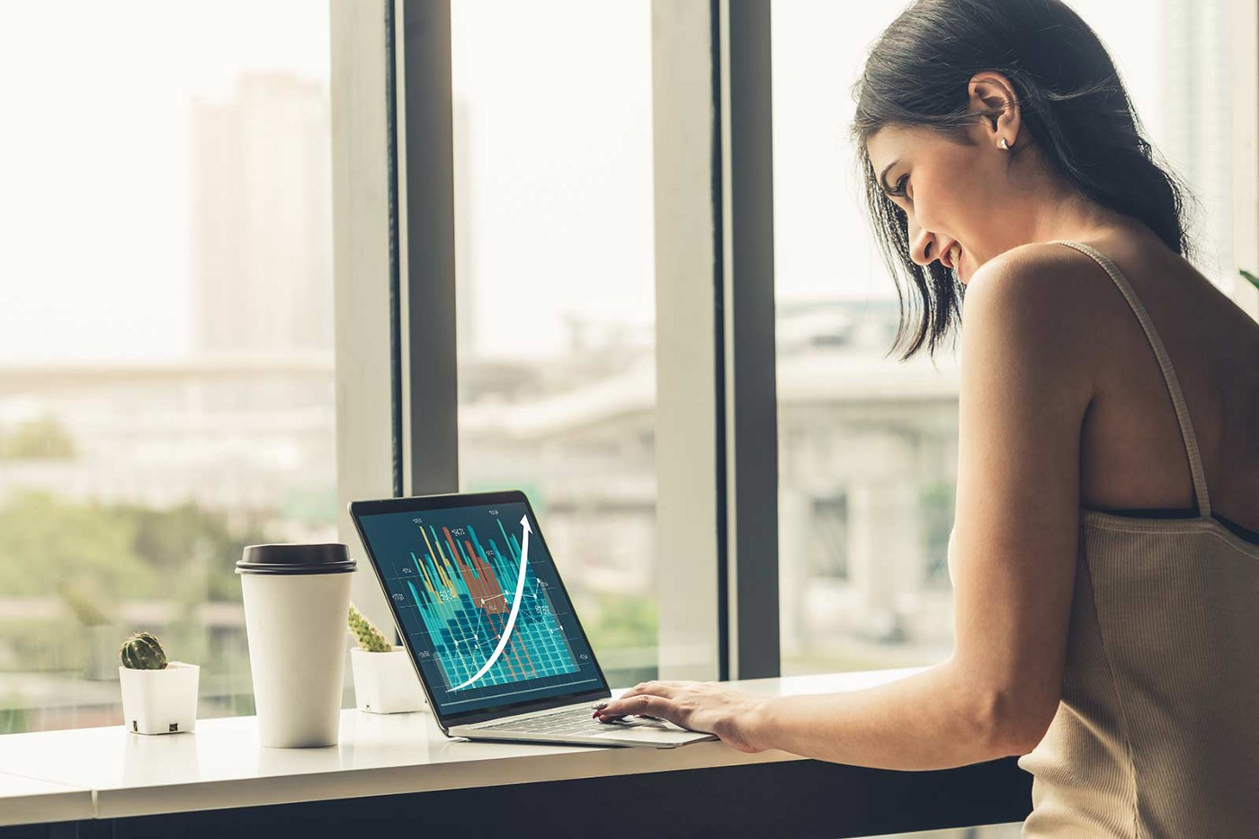 A woman reviews analytics on her laptop. A city landscape through the window is in the background.