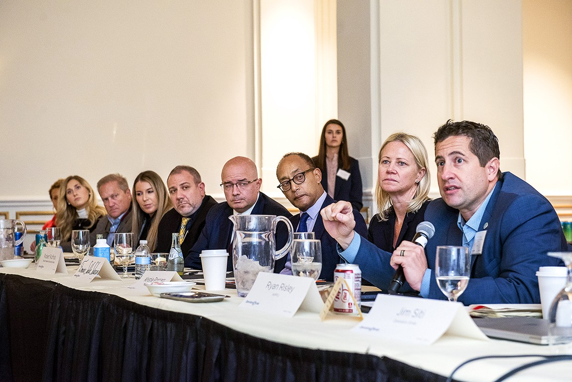 Kristie sits at a table with attendees of a government forum Operation Smile hosted.