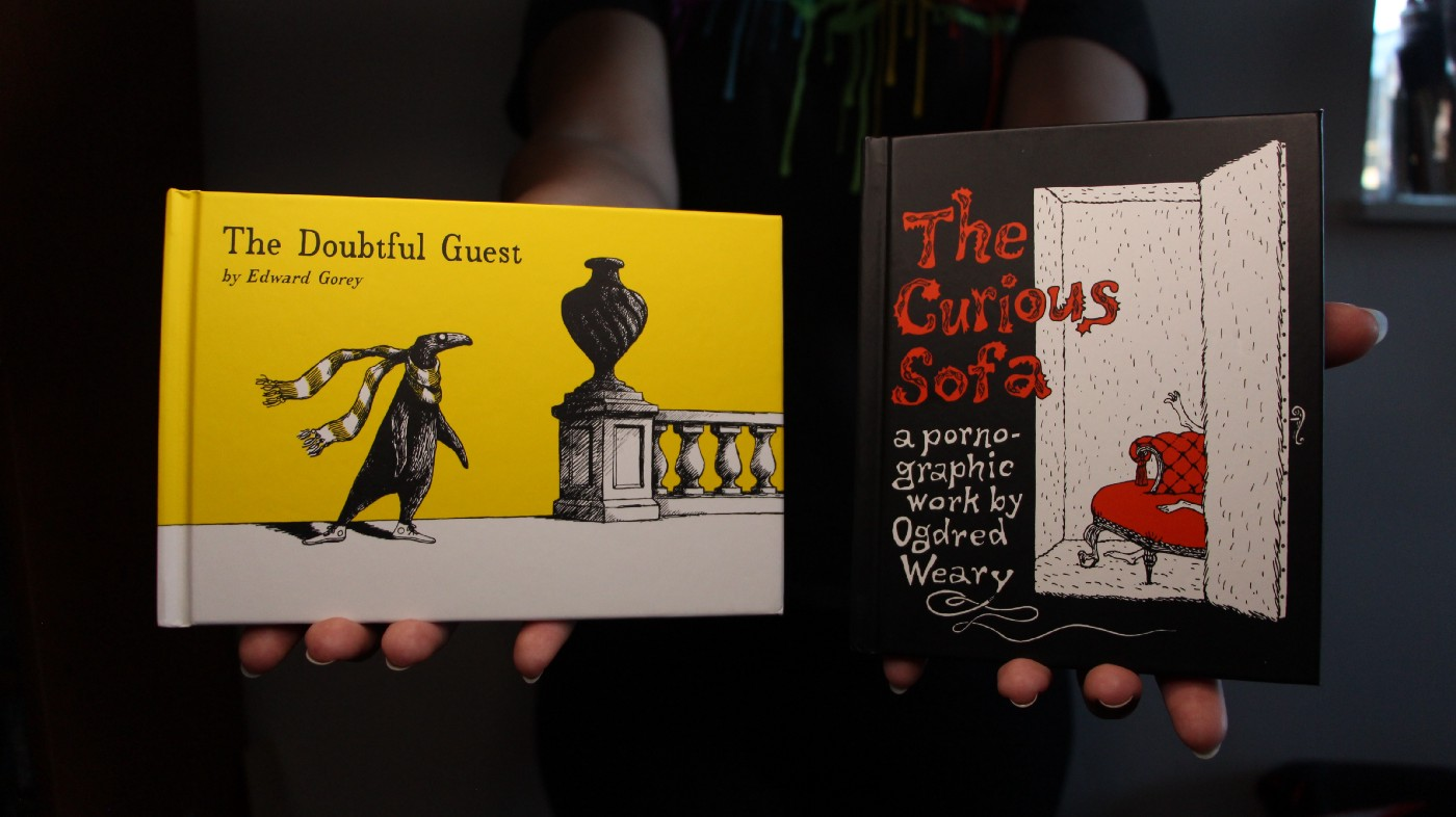 """Photographs of the covers of Edward Gorey's books, """"The Doubtful Guest"""" (1957) and """"The Curious Sofa"""" (1961), held in hands for scale. """"The Doubtful Guest"""" is bright yellow with a black penguin-like creature standing alone beside an urn and """"The Curious Sofa"""" depicts an open door showing the corner of a red sofa couch with a pair of feet visible upon it. Original photograph by Maura Wilson, MAH."""
