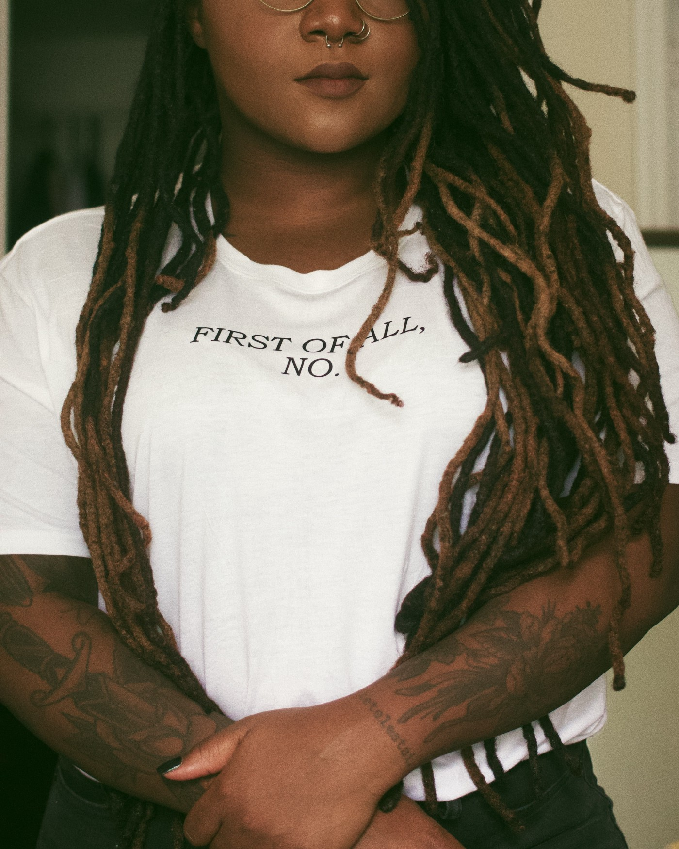 "Brown skinned Black woman with waist lenghth locs wearing a white t-shirt that says ""First of all, no."""