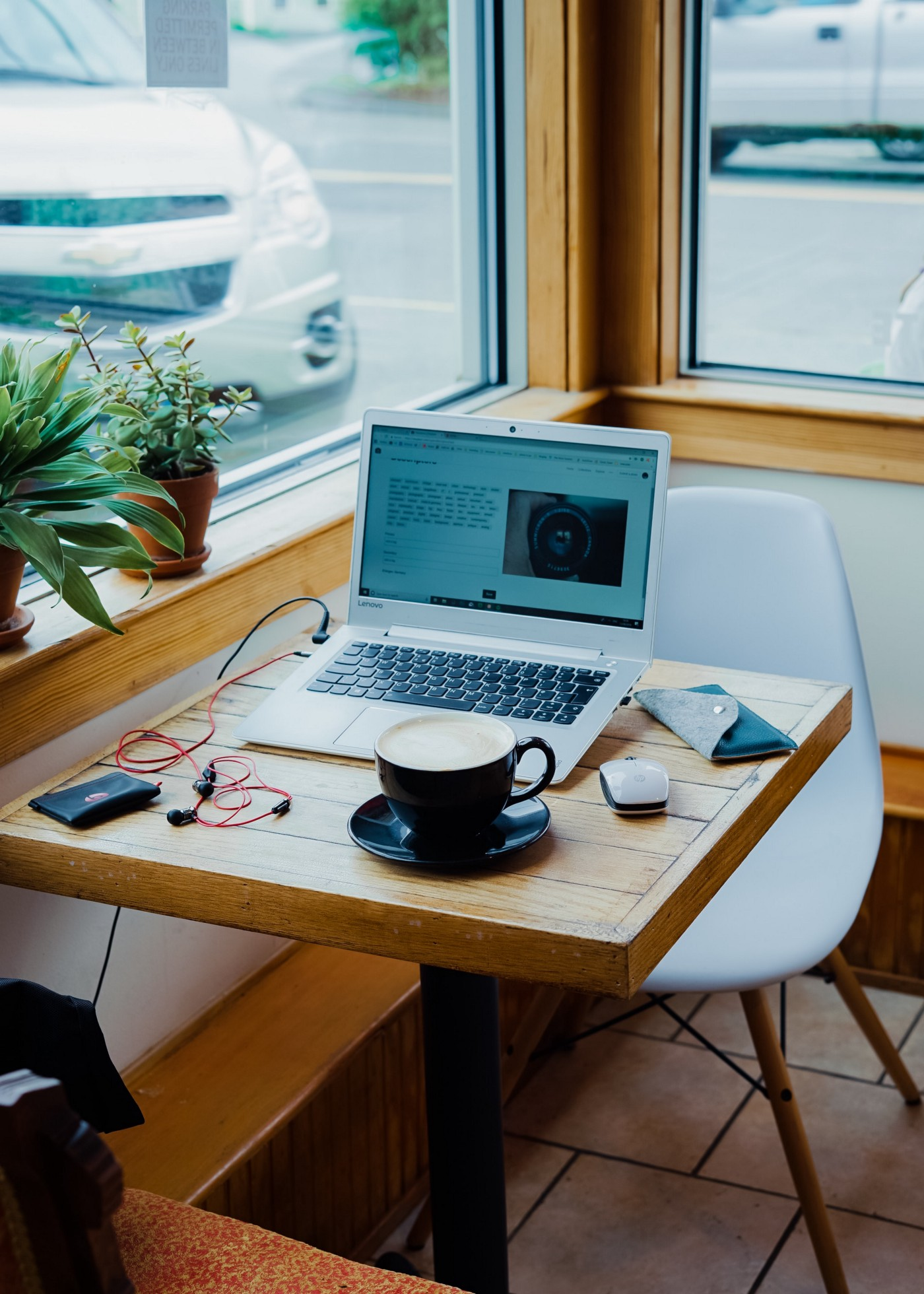 A laptop and coffee mug sitting on a table in a cafe window, the freelance life