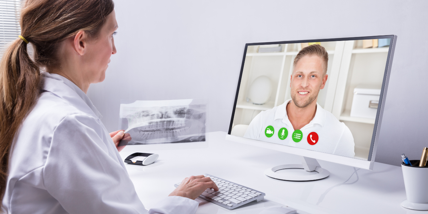 A dentist speaks to her male patient on a video conference call.